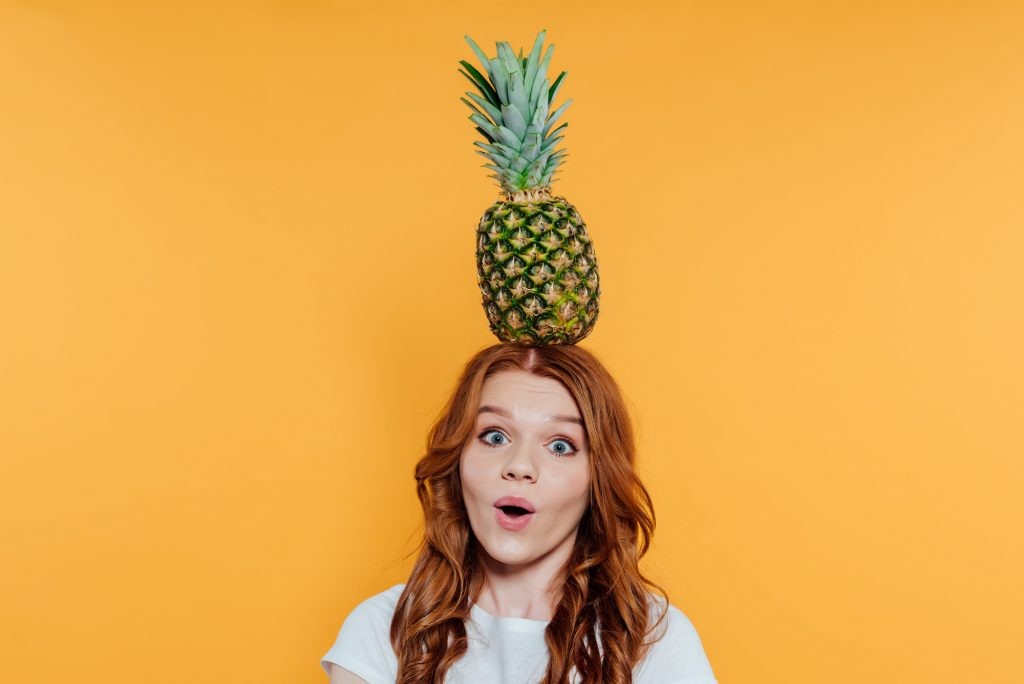 Surprised redhead girl looking at camera and posing with pineapple on head