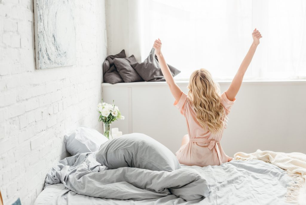 Back view of young woman with outstretched hands sitting on bed
